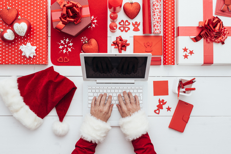 Santa Claus connecting online with a laptop, decorations and gifts, Christmas and holidays concept, flat lay