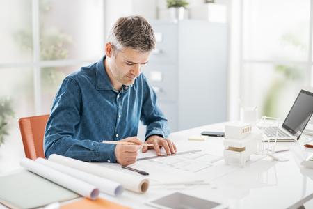 Architetto professionista che lavora alla scrivania, sta disegnando e facendo misurazioni su un progetto di progetto, progetto e concetto di architettura