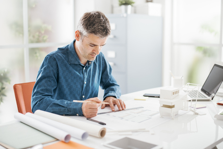 Arquitecto profesional que trabaja en el escritorio de la oficina, está dibujando y haciendo mediciones en un proyecto de proyecto, diseño y concepto de arquitectura.