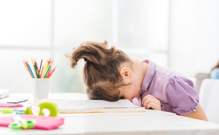 Fille étudiante paresseuse à la maison, elle se repose avec son visage vers le bas sur le livre de l'école, l'éducation et le concept de l'enfance Banque d'images - 88364357
