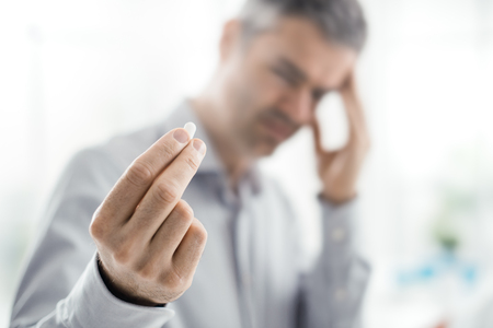 Stressed tired man with headache, he is holding a pill and touching his temples Stok Fotoğraf