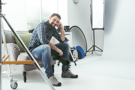 Photographer working in his studio and having a break during a photo shoot, he is smiling and holding a digital camera