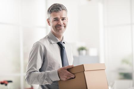 그의 새로운 사무실, 배달 및 재배치 개념으로 상자를 들고 웃는 자신감 사업가