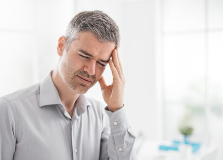 Stressed tired man having a bad headache, he is touching his temples