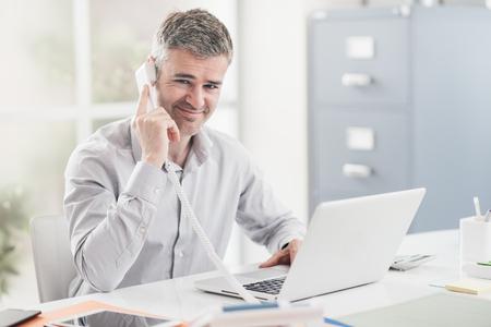 Ufny uśmiechnięty biznesmen i konsultant pracuje w jego biurze, on ma rozmowę telefonicza: komunikacyjny i biznesowy pojęcie