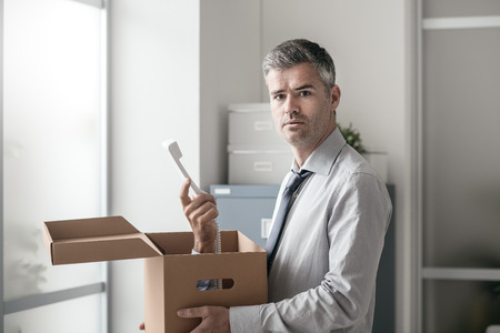 Shocked office worker receiving a surprise call inside a cardboard box, stressful job and stalking concept