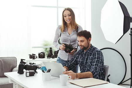 Photographer and designer working together at the creative agency, the woman is holding a camera and the man is connecting with a laptop Stock Photo