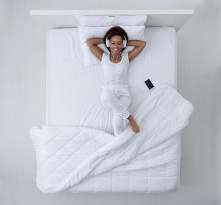 Het gelukkige Afrikaanse Amerikaanse vrouw ontspannen in bed, luistert zij aan muziek gebruikend een smartphone en hoofdtelefoons, ontspanning en koel uit concept, hoogste mening Stockfoto