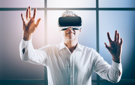 Mature man wearing a VR headset and interacting with a virtual reality environment Stock Photo