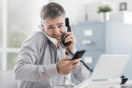 Homme d'affaires désespéré stressé travaillant dans son bureau et ayant plusieurs appels, il tient deux combinés et un téléphone portable, concept de gestion d'entreprise