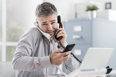 Stressed desperate businessman working in his office and having multiple calls, he is holding two handsets and a mobile phone, business management concept Archivio Fotografico