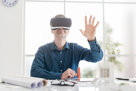 Professional architect working with virtual reality headset and interacting with a virtual environment, innovation and technology concept