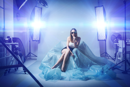 Beautiful fashion model doing a professional photo shoot, she is wearing sunglasses and an elegant dress, softboxes and flashes on the background Stock Photo