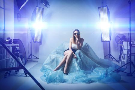Mooie mannequin die een professionele fotoshoot doet, draagt ??zij zonnebril en een elegante kleding, softboxes en flitsen op de achtergrond