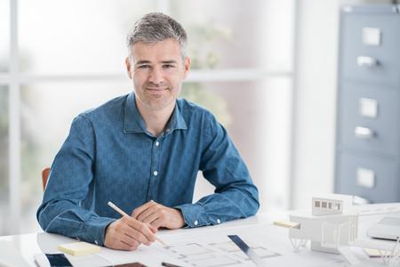 プロの建築家が座っている事務机で作業、彼はプロジェクトの設計、エンジニア リング、アーキテクチャの概念をチェック
