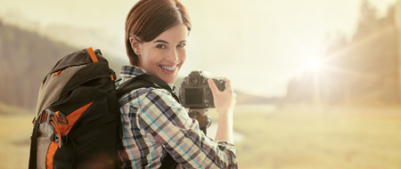 Professional hiker and photographer shooting in nature with a digital camera and a tripod, she is smiling at camera Stock fotó