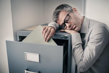 Zmęczony leniwy pracownik biurowy oparty o szafkę na dokumenty i śpiący, zasypia, wstając; stres, nieproduktywność i zaburzenia snu