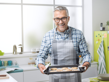 Smiling man posing in the kitchen and holding delicious freshly baked cookies, healthy homemade food and lifestyle concept Zdjęcie Seryjne