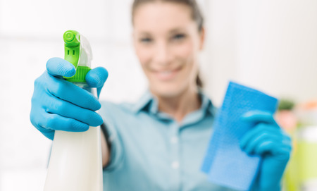 Smiling young housewife doing chores and spraying a cleaning product, hand and bottle close up, selective focus