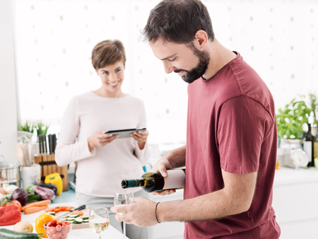 Young happy couple at home preparing lunch together, the woman is connecting with a digital tablet and her husband is pouring wine in a wineglass, relationships and lifestyle concept
