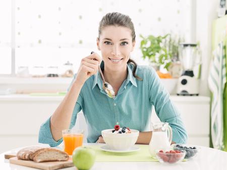 Die lächelnde glückliche Frau, die zu Hause ein entspannendes gesundes Frühstück am Küchentisch sitzt, isst sie Getreide mit Frucht und Jogurt