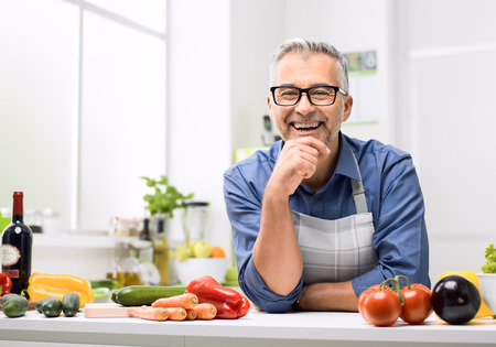 Smiling man posing in the kitchen, he is preparing healthy homemade food using fresh organic vegetables
