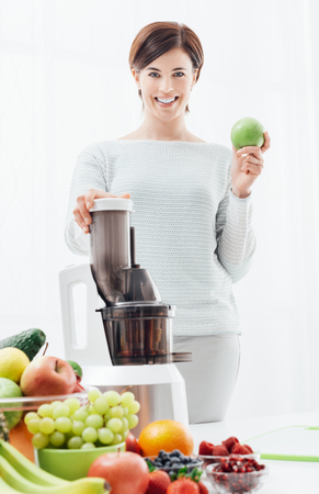 Smiling young woman holding a fresh apple and using a juice extractor, she is preparing healthy drinks with fruit and vegetables