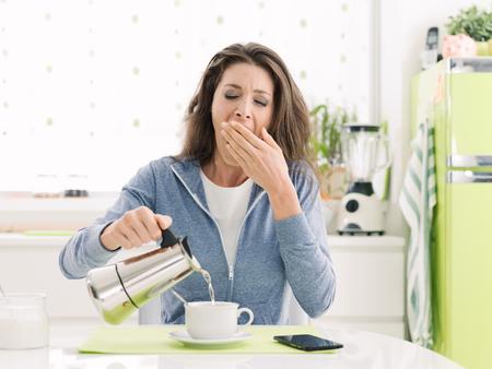 Vermoeide luie vrouw die ontbijt thuis in de keuken heeft, geeuwt zij en giet koffie