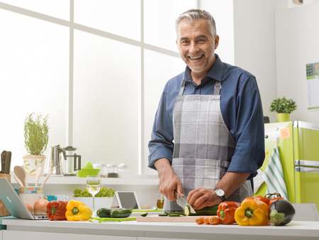 Smiling mature man cooking in the kitchen at home, he is wearing an apron and slicing fresh vegetables, healthy lifestyle concept Reklamní fotografie