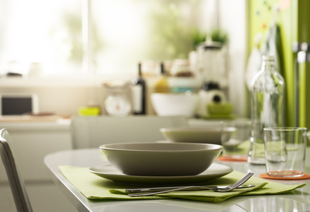 Modern kitchen interior, table setting, dishware and flatware on the foreground Archivio Fotografico