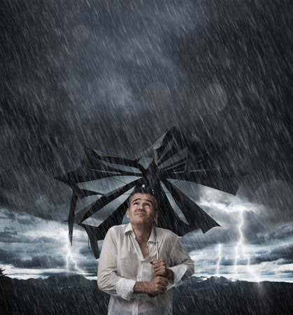 Disappointed man with broken umbrella after an unexpected storm, he is wet and dripping Stock Photo