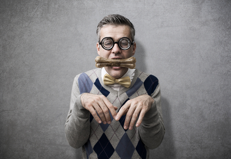 Submissive man acting like a dog and holding a bone in his mouth, obedience and humiliation concept Stock Photo