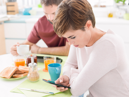 Young couple having breakfast at home, they are using mobile devices, social networking and avoiding interaction: new technologies and social isolation concept