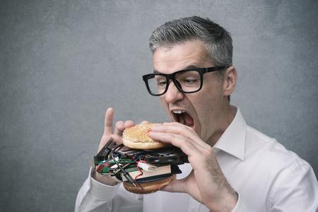 탐욕스러운 괴상한 IT 기술 애호가가 하드웨어 및 컴퓨터 부품으로 가득 찬 샌드위치를 먹고 있습니다.