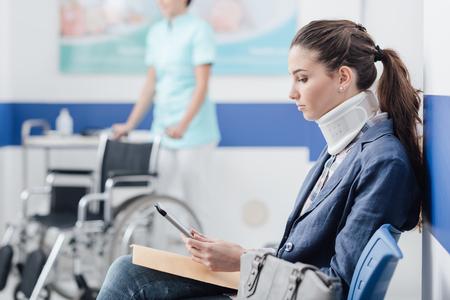 Junge Patientin mit Halskragenstütze am Krankenhaus, sitzt sie im Warteraum und schließt an eine digitale Tablette, das medizinische Personal an, das an dem Hintergrund arbeitet