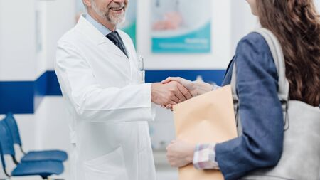 Professional smiling doctor welcoming a young female patient at the clinic, they are shaking hands Stock fotó