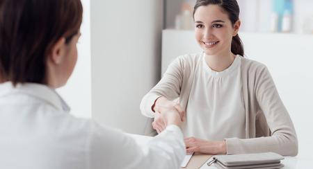 여성 의사와 사무실에서 젊은 웃는 환자, 그들은 악수하고있다