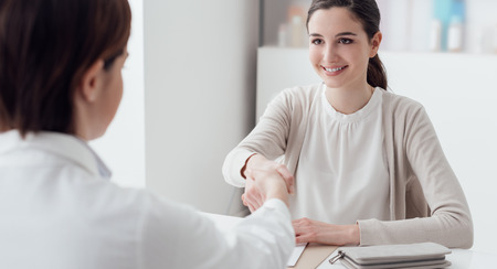 Vrouwelijke arts en jonge glimlachende patiënt in het kantoor, schudden zij handen