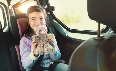 Cheerful girl sitting in a car and holding her teddy bear  Stock fotó