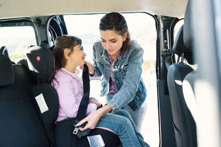 Vrouw die haar dochter helpen om veiligheidsgordels in de auto vast te maken, zit het meisje op een autokinderzitje van het veiligheidskind