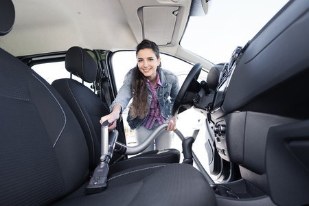 Young smiling woman cleaning the car interiors, she is vacuuming the seats upholstery with a vacuum cleaner