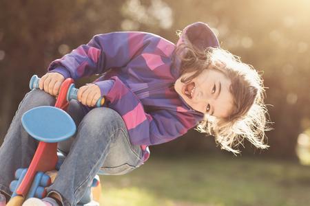 놀이터에서 행복 쾌활 한 소녀, 그녀는 봄 라이더 오토바이 타고 재미