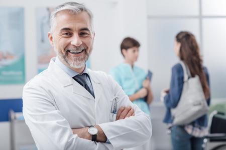 자신감이 웃는 의사가 병원에서 포즈와 배경에 환자를 환영 간호사를 넘어 스톡 콘텐츠