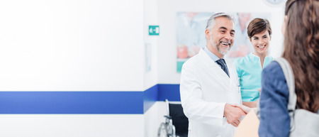 Doctor and female patient meeting at the hospital and shaking hands, healthcare and medicine banner