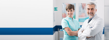 Professional medical staff posing in the hospital aisle, they are smiling at camera, healthcare workers banner Stock Photo