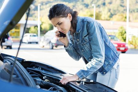 若い女性彼女のスマート フォンは、彼女の車で車支援サービスを呼び出すがこわれました 写真素材