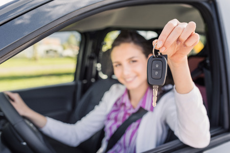 Young smiling woman sitting in a car and showing her new car keys