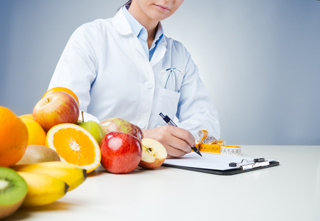 Professional nutritionist working at desk and writing medical records with fresh fruit on foreground Stockfoto