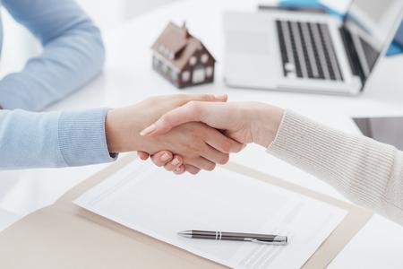 Versicherungsagent und -kunde, die Hände rütteln, nachdem ein Vertrag unterzeichnet worden ist: Immobilien-, Wohnungsbaudarlehen- und Versicherungskonzept