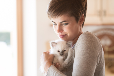Young smiling woman hugging and cuddling her cute kitten, pets and lifestyle concept